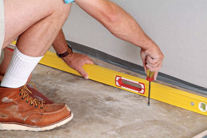 Set the screw head nearest the floor's high point about 1/8 in. above the floor.